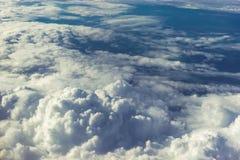 在天堂概念、看法从飞机到蓬松白色云彩和蓝色大气,自然地平线风景上 免版税库存图片