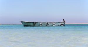 在天堂海岛上的木小船红色的看见,有船员的埃及 免版税图库摄影
