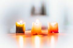 在天堂般的气氛包围的三个灼烧的蜡烛 库存照片