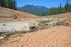 在天旱期间,烘干河,在距离的山的破裂的床 库存照片