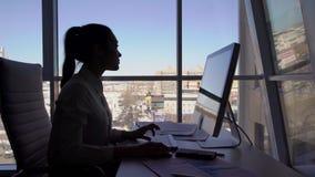 在天期间,在键盘的女性剪影工作在窗口附近在办公室屋子里 股票视频