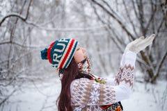 在天期间,微笑的女孩照片被编织的帽子和围巾传染性的雪花的在冬天森林里 图库摄影