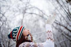 在天期间,微笑的女孩照片被编织的帽子和围巾传染性的雪花的在冬天森林里 库存照片