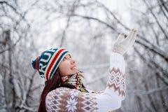 在天期间,微笑的女孩照片被编织的帽子和围巾传染性的雪花的在冬天森林里 免版税库存图片
