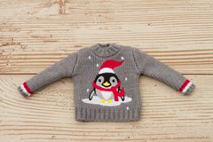 在天气木头Backgro的灰色和红色企鹅圣诞节毛线衣 库存照片