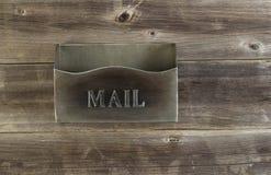 在天气木头的空的老金属邮箱 免版税库存照片