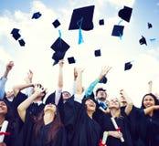 在天空中投掷的毕业盖帽 库存图片