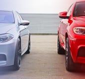 在天空和金属篱芭背景的第两部分汽车  肩并肩站立两辆的汽车 库存照片