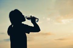 在天空日落的剪影妇女饮用水 库存照片