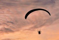 在天空日落背景的滑翔伞飞行 库存图片