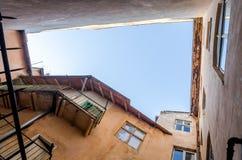 在天空的一个孔在屋顶在与阳台、窗口和进口的老历史建筑崩溃了在街道  库存图片