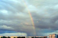 在天空的一条五颜六色的彩虹在城市 在雨以后 免版税库存图片