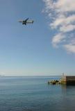 在天空的一架飞行飞机在海洋上 免版税库存图片
