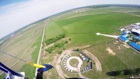 在天空的专业跳伞运动员飞行在路上 晴朗 登陆在绿色领域 股票录像
