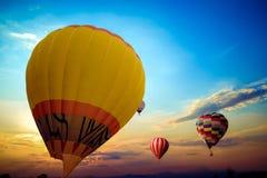 在天空的五颜六色的热空气气球飞行在日落 库存照片