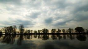 在天空的剧烈的云彩在日落时间 开始的雨做与远的河岸的反射的浪潮起伏的水表面与 股票视频