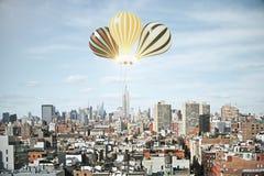 在天空的发光的baloons在megapolis城市上 图库摄影