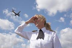 在天空的女性试验观看的喷气式客机 免版税库存图片