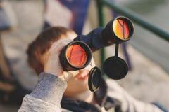 在天空的小男孩观看的飞机由双筒望远镜 库存照片