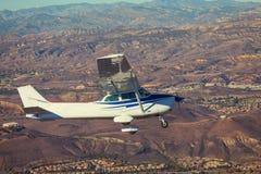 在天空的小飞机飞行在山 免版税图库摄影