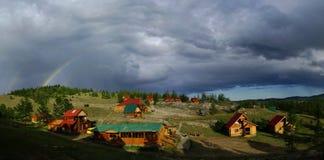 在天空的彩虹在下小山的小的房子 免版税库存照片