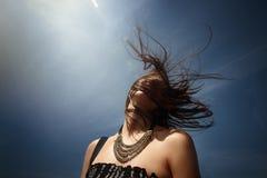 在天空的愉快的时髦的妇女行家头与有有风的头发 免版税图库摄影