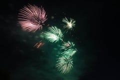 在天空的桃红色和绿色烟花 免版税库存照片