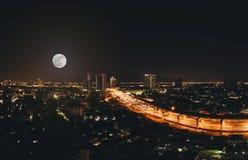 在天空的满月在美丽的城市在晚上 免版税库存照片