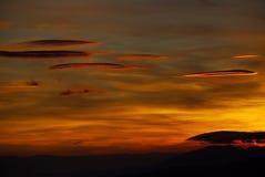 在天空的火 盘旋的双突透镜的云彩,点燃由西班牙日落 免版税库存照片