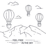 在天空的热空气气球在白色背景的山下 图库摄影