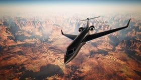 在天空的照片黑表面无光泽的豪华普通设计私人喷气式飞机飞行在地面下 全部背景的峡谷 图库摄影