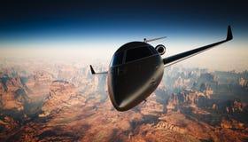 在天空的特写镜头黑表面无光泽的豪华普通设计私人喷气式飞机飞行在地面下 全部背景的峡谷 库存图片