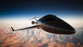 在天空的特写镜头黑表面无光泽的豪华普通设计私人喷气式飞机飞行在地面下 全部背景的峡谷 图库摄影