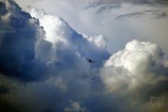 在天空的狂放的风雨如磐的云彩与飞机 库存照片