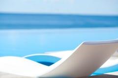 在天空的白色长的椅子 免版税库存图片