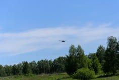 在天空的直升机在森林上 免版税库存图片