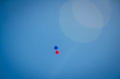 在天空的红色和蓝色气球 免版税库存照片