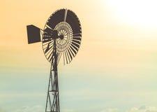 在天空的老水泵风车在日落 免版税库存图片