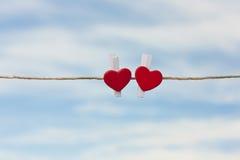 在天空的背景的两红色心脏 库存图片
