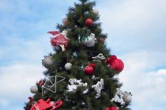 在天空的背景的圣诞树,一棵美丽的圣诞树用红色袋子和鹿装饰在正方形 库存图片