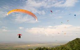 在天空的许多滑翔伞反对云彩,与一个接近观察者 库存图片