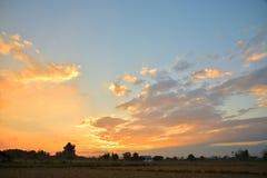 在天空的金黄光在日落期间在晚上 免版税库存图片