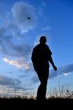 在天空的风筝 一个人的剪影,从地面的看法 图库摄影