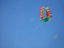 在天空的风筝 上色船在天空的风筝飞行在一个明亮的晴天 库存照片