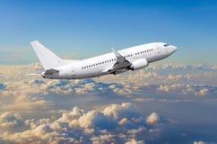 在天空的飞机在云彩飞行旅途太阳高度上 免版税图库摄影