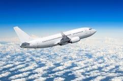 在天空的飞机在云彩飞行旅途太阳高度上 免版税库存照片