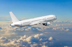 在天空的飞机在云彩飞行旅途太阳高度上 库存图片