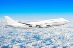 在天空的飞机在云彩飞行旅途太阳高度上 库存照片