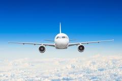 在天空的飞机在云彩飞行旅途太阳高度上 免版税库存图片