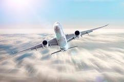 在天空的飞机在云彩飞行旅途太阳高度速度行动迷离上 免版税图库摄影